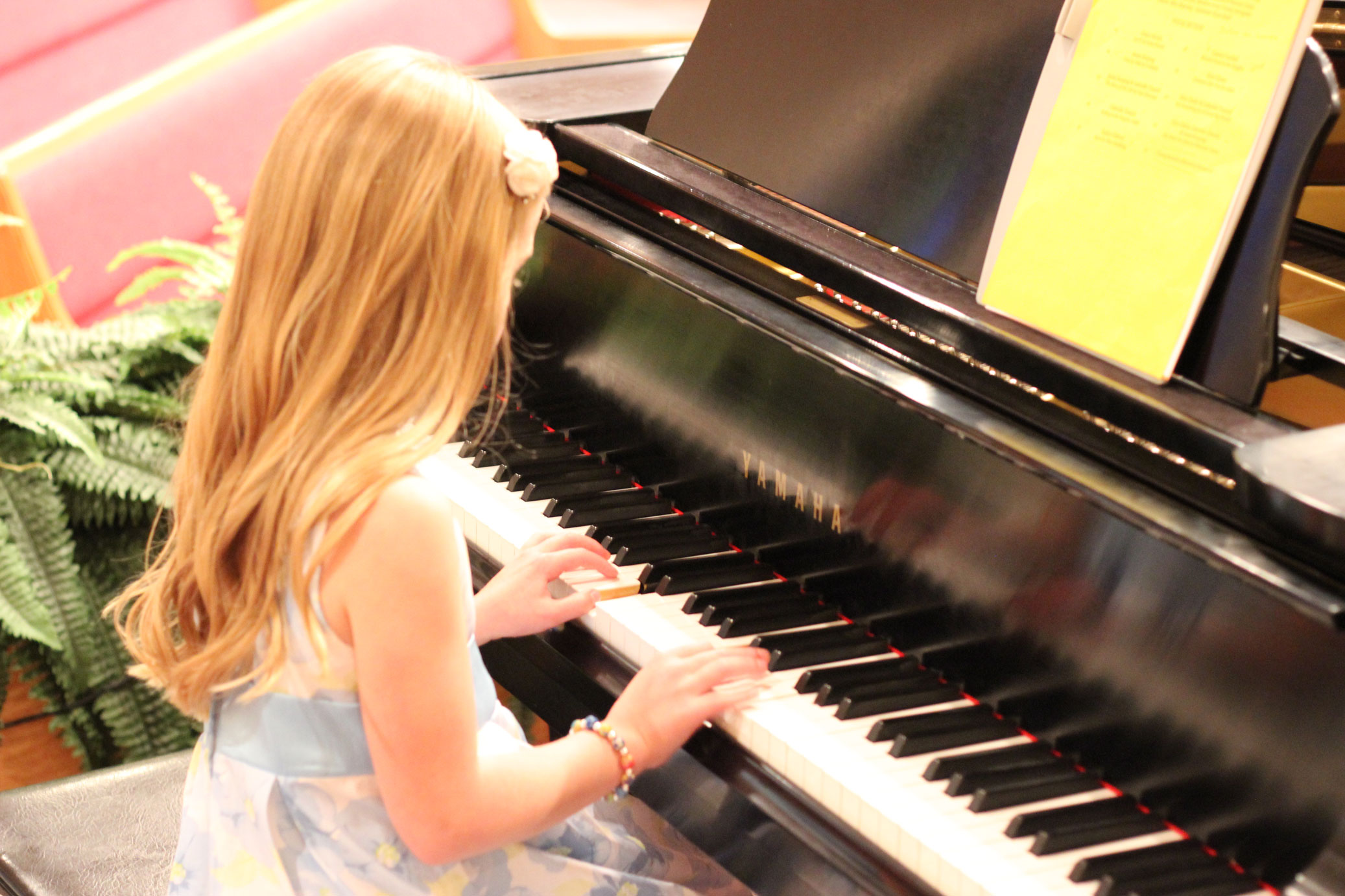 Young student Katelyn performing her piece at the recital